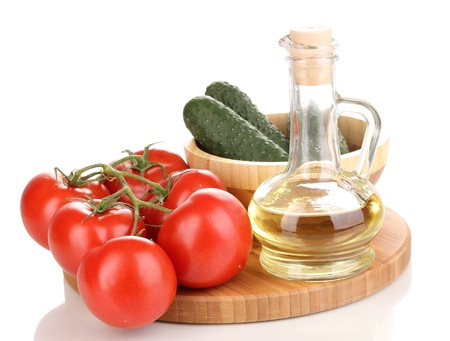 Tomatoes and cucumbers with oil on wooden board isolated on white photo