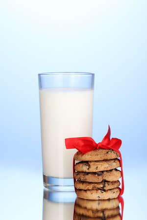 Glass of milk and cookies on blue background Stock Photo - 13942871