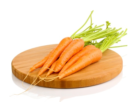 Carrots on wooden board isolated on white photo