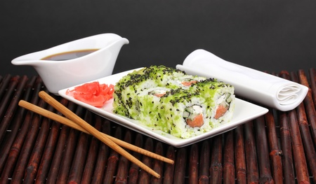 Tasty rolls served on white plate with chopsticks on bamboo mat on black background photo