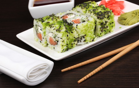 Tasty rolls served on white plate with chopsticks on wooden table close-up photo