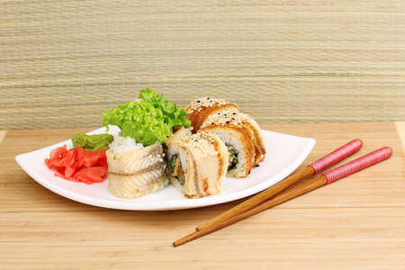 Tasty rolls served on white plate with chopsticks on wooden table on light background Stock Photo - 13944614
