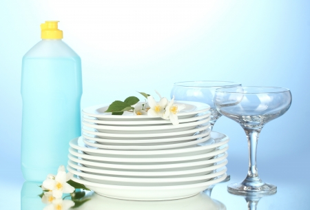 empty clean plates and glasses with dishwashing liquid on blue background photo