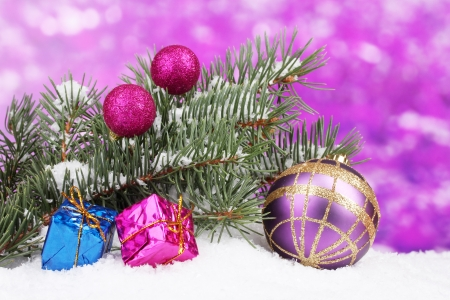 Christmas ball and toy with green tree in the snow on purple Stock Photo - 13944654