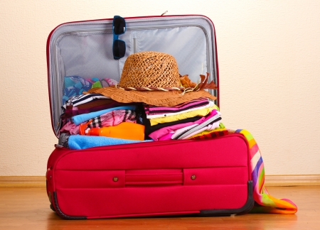 belongings: Open red suitcase with clothing in the room