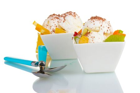 delicious vanilla ice cream with chocolate and fruits in bowls and spoons isolated on white photo