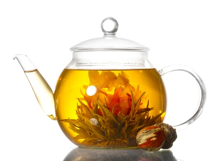 red tea: exotic green tea with flowers in glass teapot isolated on white Stock Photo