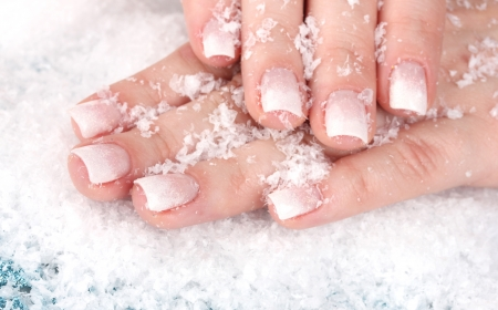 beautiful hands with snow closeup photo