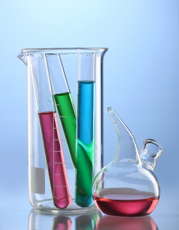 Laboratory glassware with color liquid and with reflection on blue background photo