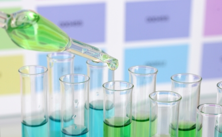 Test-tubes with color liquid and pipette on color samples background photo