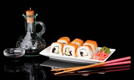Tasty rolls served on white plate with chopsticks and soy sauce isolated on black photo
