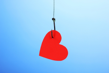 Heart on fish hook on blue background photo