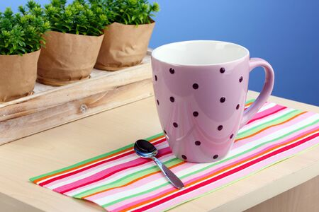 Coffee cup on table in cafe on blue background photo