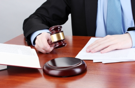 golden rule: wooden gavel in hand and books on wooden table on gray background