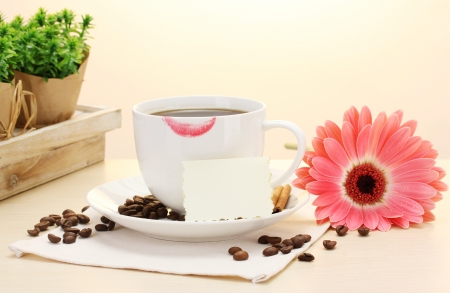 cup of coffee with lipstick mark and gerbera beans, cinnamon sticks on wooden table Stock Photo - 13943041