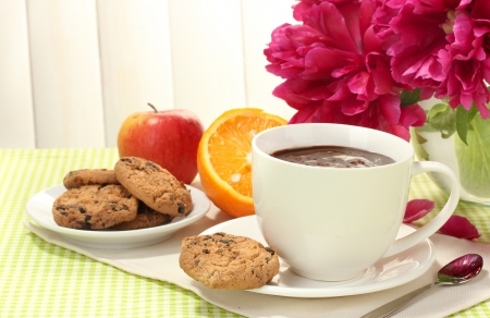 cup hot chocolate, apple, orange, cookies and flowers on table in cafe photo