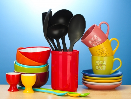 kitchen tool: bright empty bowls, cups and kitchen utensils on wooden table on blue background