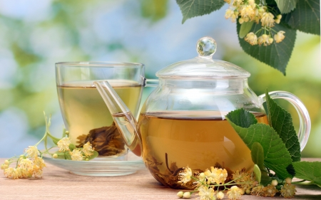 linden tea: teapot and cup with linden tea  and flowers on wooden table in garden  Stock Photo