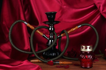 hookah on a wooden table on a background of red curtain close-up photo