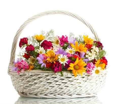 arreglo floral: hermoso ramo de flores silvestres brillantes en la canasta, aislados en blanco Foto de archivo