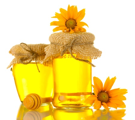Sweet honey in jars with wooden drizzler and flowers isolated on white photo