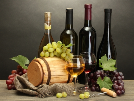white wine bottle: barrel, bottles and glasses of wine and ripe grapes on wooden table on grey background Stock Photo
