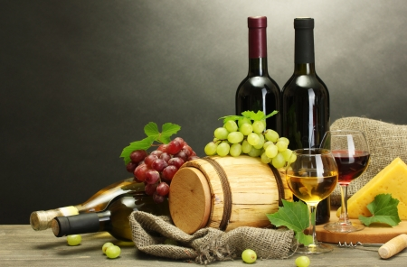 barrel, bottles and glasses of wine, cheese and ripe grapes on wooden table on grey background Stock Photo - 14013973