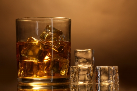 whisky: glass of whiskey and ice on brown background