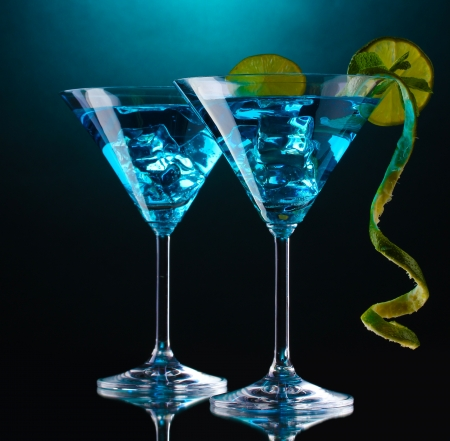 gin: Blue cocktail in martini glasses on blue background