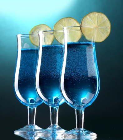 Blue cocktail in glasses with lime on blue background photo