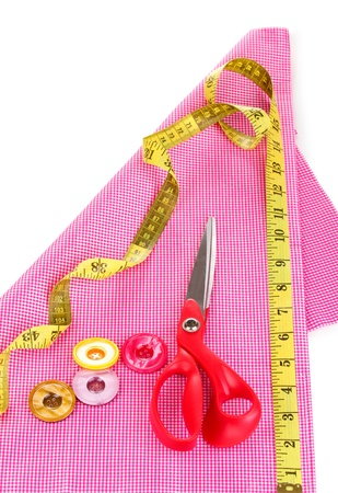 Scissors, buttons, measuring tape and pattern on fabric isolated on white photo