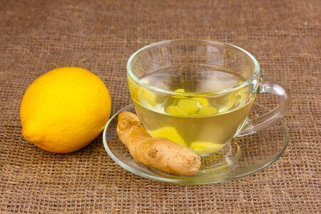 Healthy ginger tea with lemon on sackcloth photo
