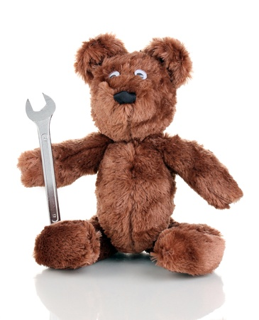 Sitting bear toy with wrench isolated on white photo
