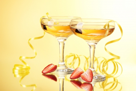 glasses of champagne and strawberries on yellow background photo