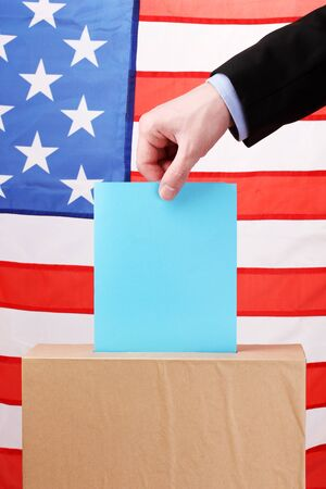 Hand with voting ballot and box on Flag of USA photo