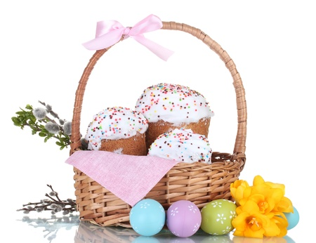 Beautiful Easter cakes in basket, colorful eggs and flowers isolated on white photo