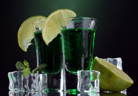 ajenjo: Dos vasos de absenta, lima y hielo sobre fondo verde