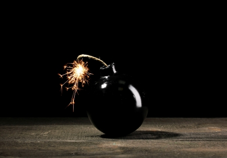 Cartoon style bomb on wooden table on black background Stock Photo - 13998102