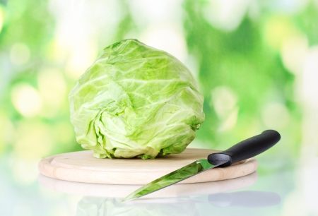 Cabbage on a cutting board with knife on colorful green background