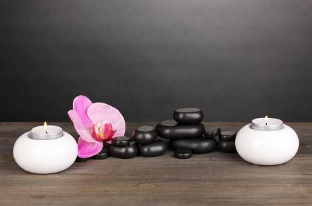 Spa stones with orchid flower and candles on wooden table on grey background photo