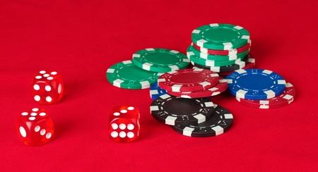 Poker chips wirh dice on a red table photo
