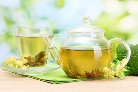 Teekanne und Tasse mit linden Tee und Blumen auf Holztisch im Garten