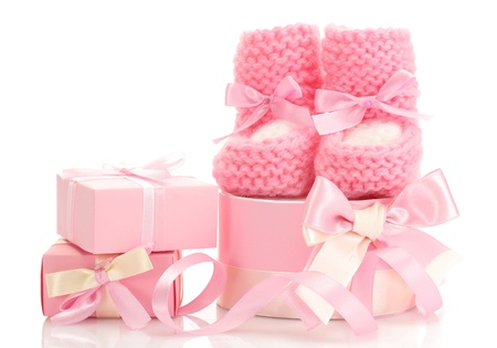 pink baby boots and gifts isolated on white photo