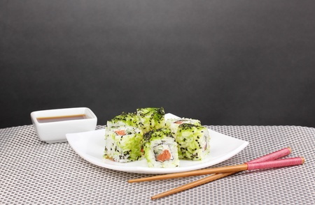 Tasty rolls served on white plate with chopsticks on grey mat on grey background photo