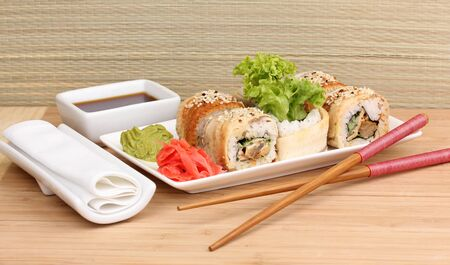 Tasty rolls served on white plate with chopsticks on wooden table on light background Stock Photo - 14052618