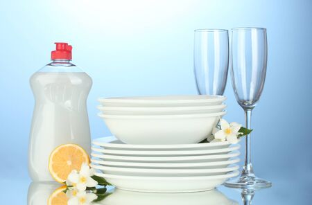 empty clean plates and glasses with dishwashing liquid and lemon on blue background photo