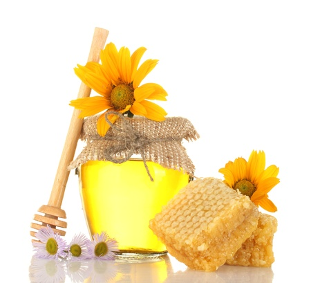 Sweet honey in jar with honeycomb, wooden drizzler and flowers isolated on white photo