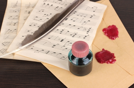 Musical notes and feather on wooden table photo