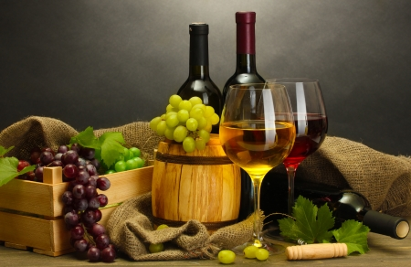 barrel, bottles and glasses of wine and ripe grapes on wooden table on grey background Stock Photo - 14072590
