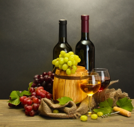barrel, bottles and glasses of wine and ripe grapes on wooden table on grey background Stock Photo - 14070145
